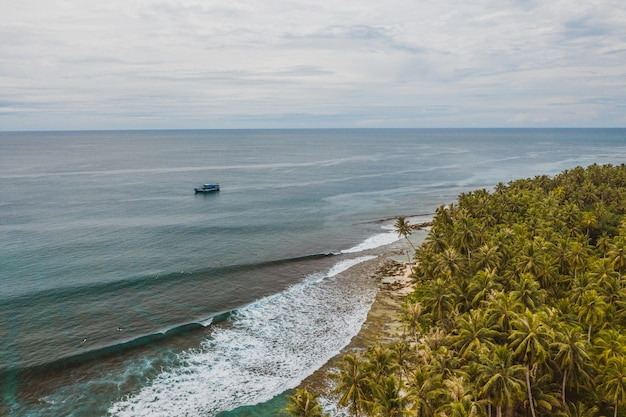 インドネシアの白い砂浜とターコイズブルーの澄んだ水で魅惑的な海岸線の景色