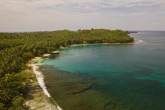 インドネシアの白い砂浜とターコイズブルーの澄んだ水で海岸線の魅惑的な景色