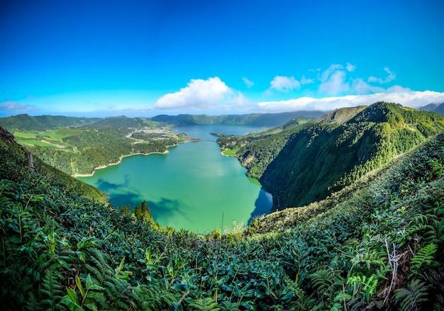 Завораживающий вид на озеро, окруженное зелеными горами под голубым небом.