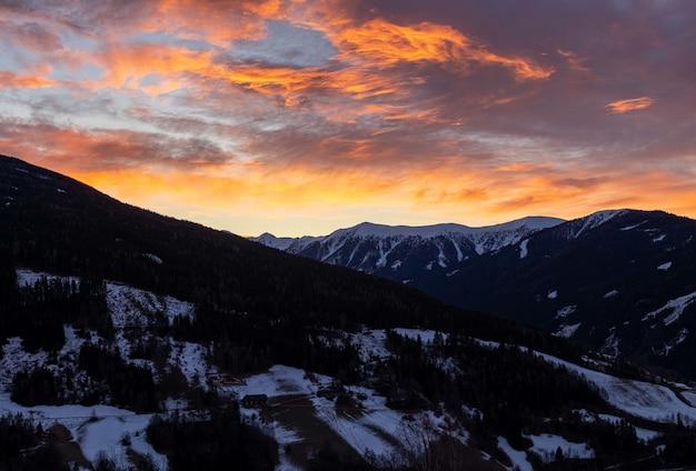 日の出中に雪に覆われた山々の魅惑的なビュー