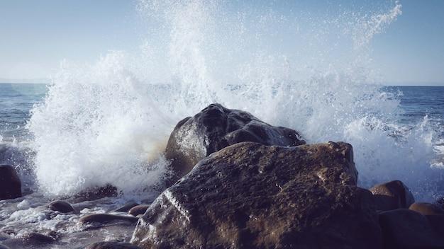 해안 근처의 바위에 부서지는 파도의 매혹적인 전망