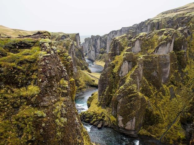 青い空の下の崖を流れる川の魅惑的な景色