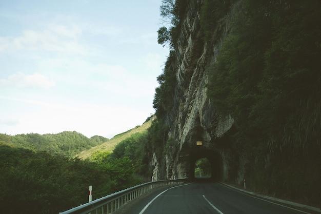 나무와 산으로 둘러싸인 바위 절벽 아치를 통해 도로의 매혹적인 전망