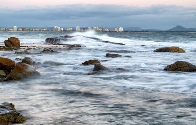 Rostock, 독일의 kap geinitzort에서 바위 해변 너머로 일몰의 매혹적인 전망
