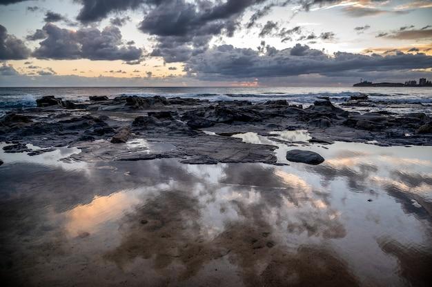 독일 rostock의 kap geinitzort에 있는 바위 해변 위로 일몰의 매혹적인 전망