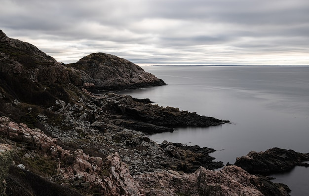 Mesmerizing view of a rocky shore and a calm sea on a gloomy day