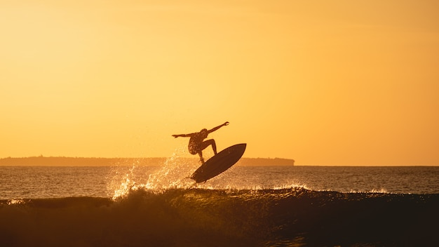 Mesmerizing view of the silhouette of a surfer in the ocean during sunset in indonesia