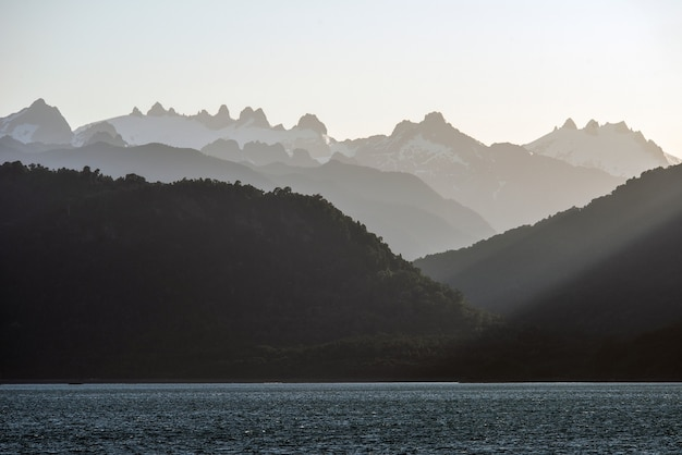 Mesmerizing view of the silhouettes of the mountains behind the calm ocean during sunset