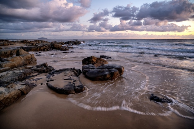 Mesmerizing view of the sunset over rocky seashore in kap geinitzort in rostock, germany