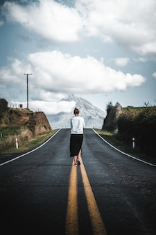 Mesmerizing view of a young tourist walking on the empty road leading to the mountain
