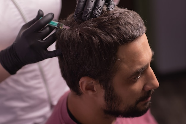 Мезотерапия для волос. привлекательный мужчина получает инъекции в голову. человек, имеющий сеанс мезотерапии в салоне красоты, терапевт в защитной перчатке со шприцем,