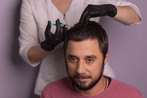 Mesotherapy for hair. attractive man receiving injections in his head. man having mesotherapy session at beauty salon, therapist in protective glove with syringe,