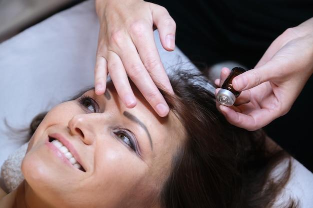 Мезотерапия, лечение волос. зрелая женщина с проблемой выпадения волос, получающей лечение в клинике, косметика для укрепления и роста волос