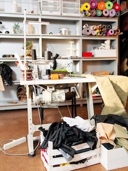 Беспорядок в швейной мастерской с портновскими инструментами и тканями.