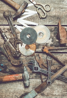 Mess of vintage carpentry tools on old wooden background