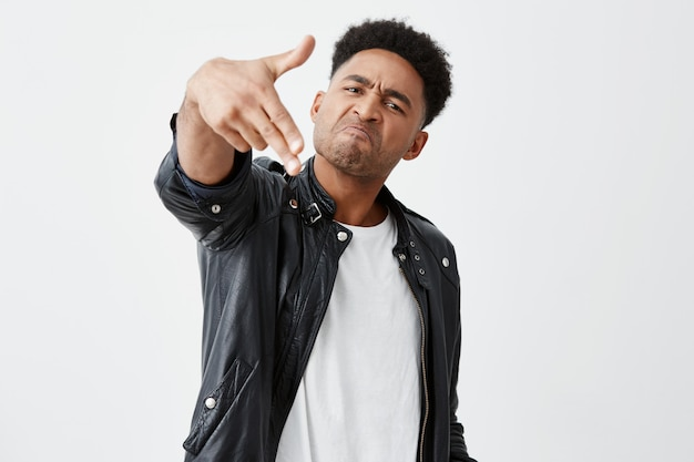 Don't mess with me, man. close up of mature dark-skinned african male student with curly hair in casual outfit showing gun gesture with hand, looking in camera with angry and mad face expression.