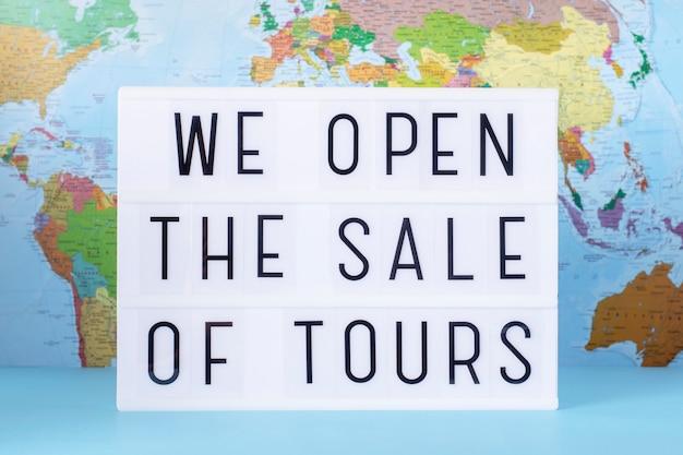 Сообщение о продаже туров. световой короб на фоне карты мира, крупным планом.