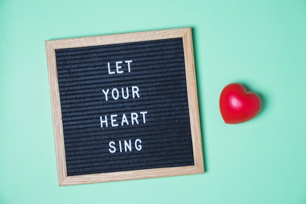 Message on board and red heart on turquoise background