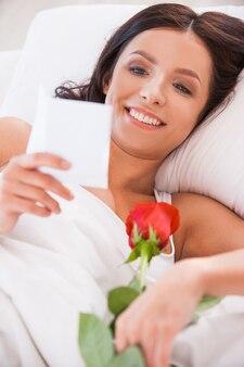 남자친구의 메시지. 빨간 장미와 함께 침대에 누워 편지를 읽는 아름다운 젊은 여성의 이미지를 클로즈업