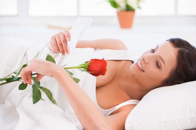 남자친구의 메시지. 빨간 장미와 함께 침대에 누워 편지를 읽는 아름다운 젊은 여성의 측면