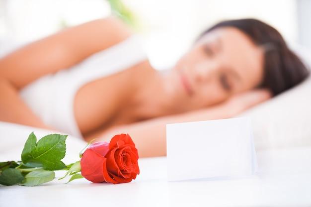 남자친구의 메시지. 빨간 장미와 함께 침대에 누워 있는 아름 다운 젊은 여자의 측면 보기