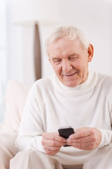 Message from nearest . happy senior man holding mobile phone while sitting in chair