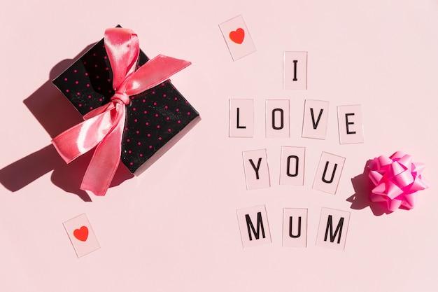 Счастливое сообщение дня матерей с красными сердцами на яркой розовой предпосылке. концепция поздравительной открытки. день матери message.gift и текст
