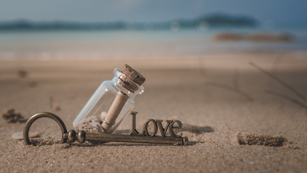 Message glass bottle and key on sea beach
