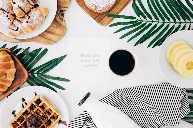 Message on notepad surrounded with baked breakfast; coffee and pineapple slices on white desk