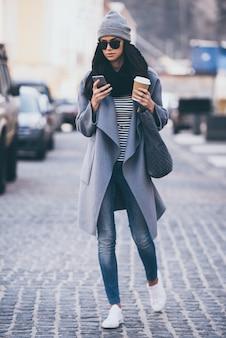 이동 중 메시지. 길을 건너는 동안 스마트 폰을 사용하여 선글라스를 쓴 아름다운 젊은 여성의 전체 길이