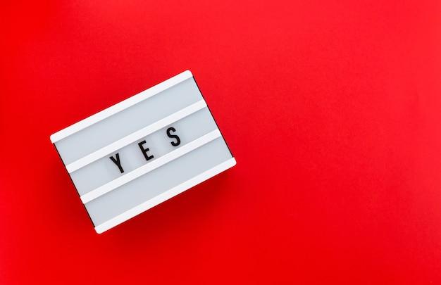 赤い背景で隔離された白いライトボックスにメッセージはい。ビジネス、モチベーション、教育のコンセプト、自分に力を与える