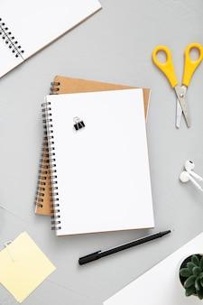 Messy arrangement of desk elements with empty notebook