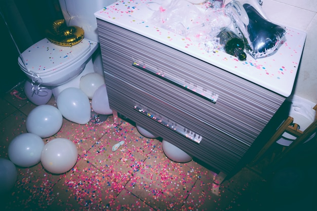 Messy bathroom with an empty bottle; colorful confetti and white balloons after the birthday party
