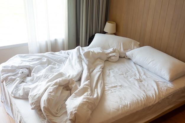 乱雑なベッド。整えられていないベッドの上の白い毛布でカップル枕。