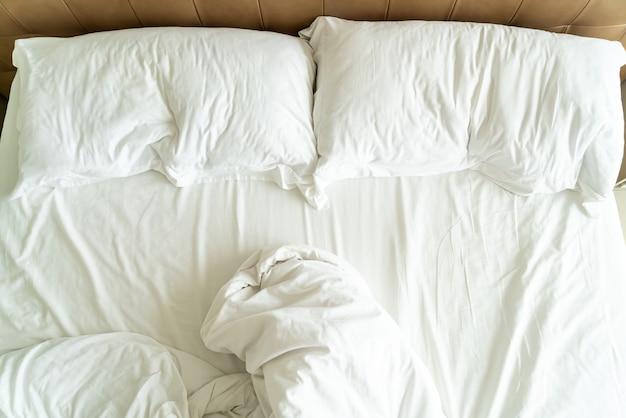 Грязная кровать с белой подушкой и одеялом на кровати