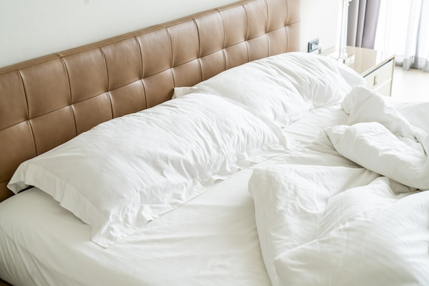 Messy bed with white pillow and blanket on bed