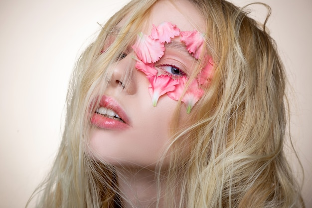 乱雑なブロンドの髪。目の近くにピンクの花でポーズをとる乱雑なブロンドの髪を持つ青い目の魅力的なモデル