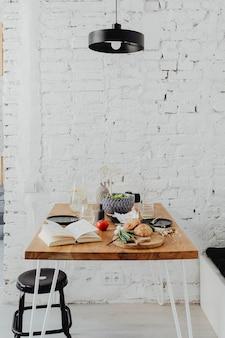 Tavolo da pranzo disordinato con un libro