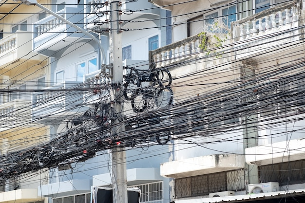 Messy electrical cables in thailand - many lines of cables chaotic set of interwoven, optical fiber technology open air outdoors.
