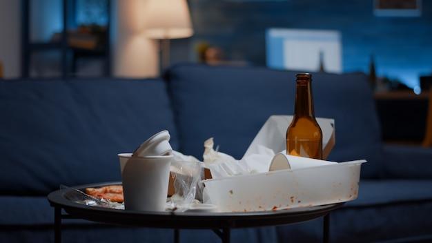 うつ病の人の散らかった空のリビングルームは、散らばった食べ物の混乱の無秩序なテーブルの整理されていない家...