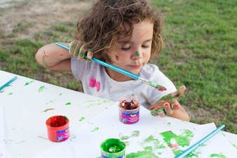 Messy girl painting on canvas in park