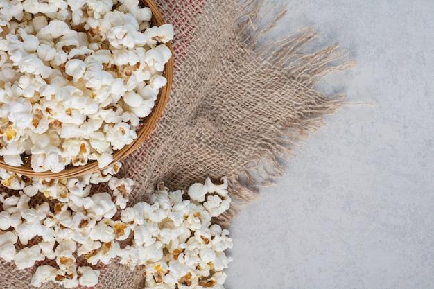 Mucchio disordinato di popcorn accanto a una ciotola piena su un pezzo di stoffa su marmo.