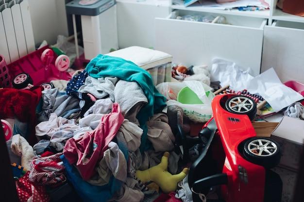 거실이나 침실의 지저분한 방과 무질서한 개념. 바닥에 흩어져 있는 옷과 물건들.