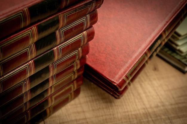 Грязные стопки старых книг на старом деревянном столе и тусклый свет. выборочный фокус. винтажная концепция сцены. копировать пространство