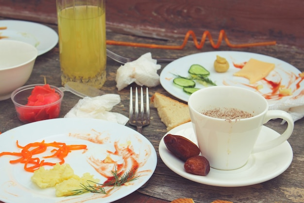 Грязный стол после вечеринки. остатки еды, пролитые напитки, грязная посуда. тонированное изображение.