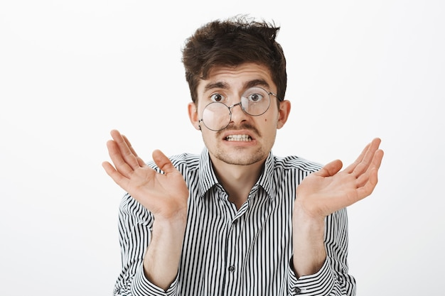 Messy untidy funny guy with moustache and beard, shrugging and raising palm, grimacing from confusion and sress, looking like garbage agter rough night, wearing glasses on side, standing questioned