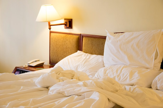 Messy white bed and pillow and lamp. Premium Photo