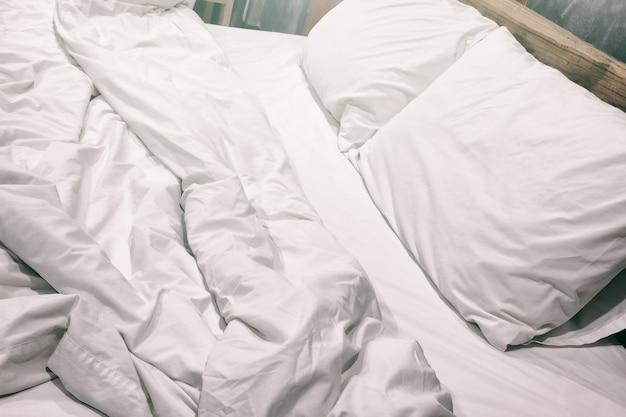 Messy white bed and two pillow, in the morning.vintage filter.