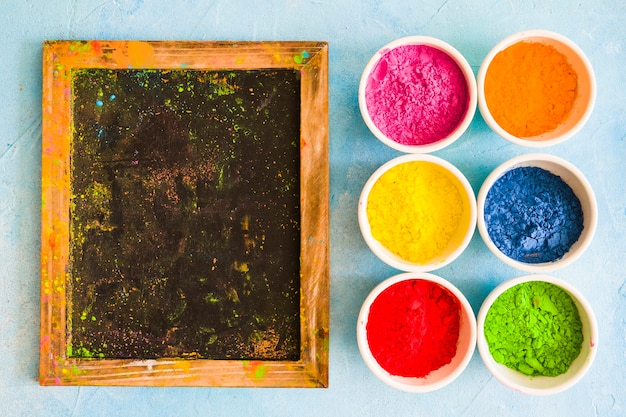 Messy wooden slate with holi color powder in the white bowls on painted backdrop