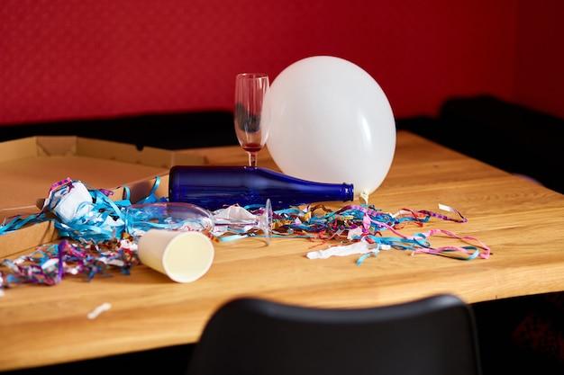 Грязный деревянный стол с коробкой для пиццы, пустыми синими бутылками, бокалом для вина и праздничными украшениями утром после празднования вечеринки, хаоса после вечеринки, остатков празднования.